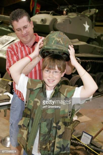 A father and son at the Veterans Memorial Museum and the young boy is trying on a military uniform