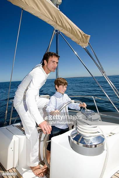 Father and son (6-8) at wheel of sailboat