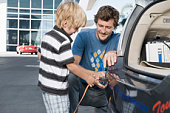 Father and son (5-6) attaching electrical plug to electric car