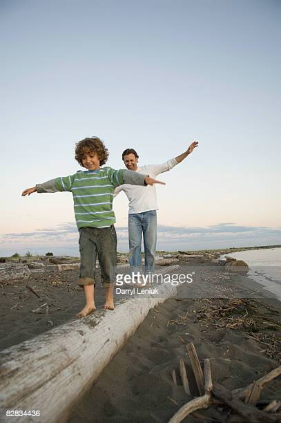 father and son balancing on log on beach