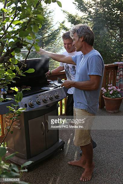 Father and son barbeque hamburgers on deck