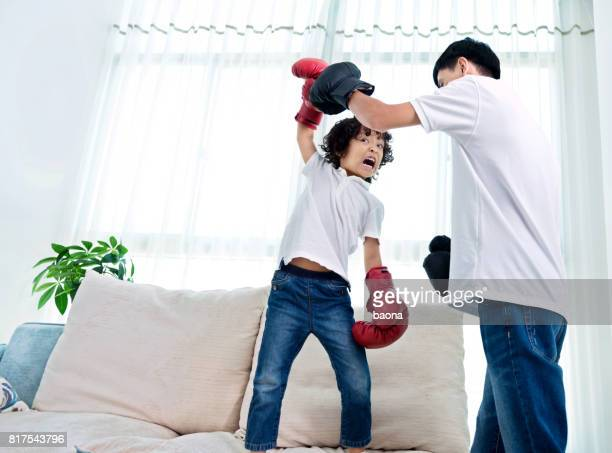 Father and son boxing at home
