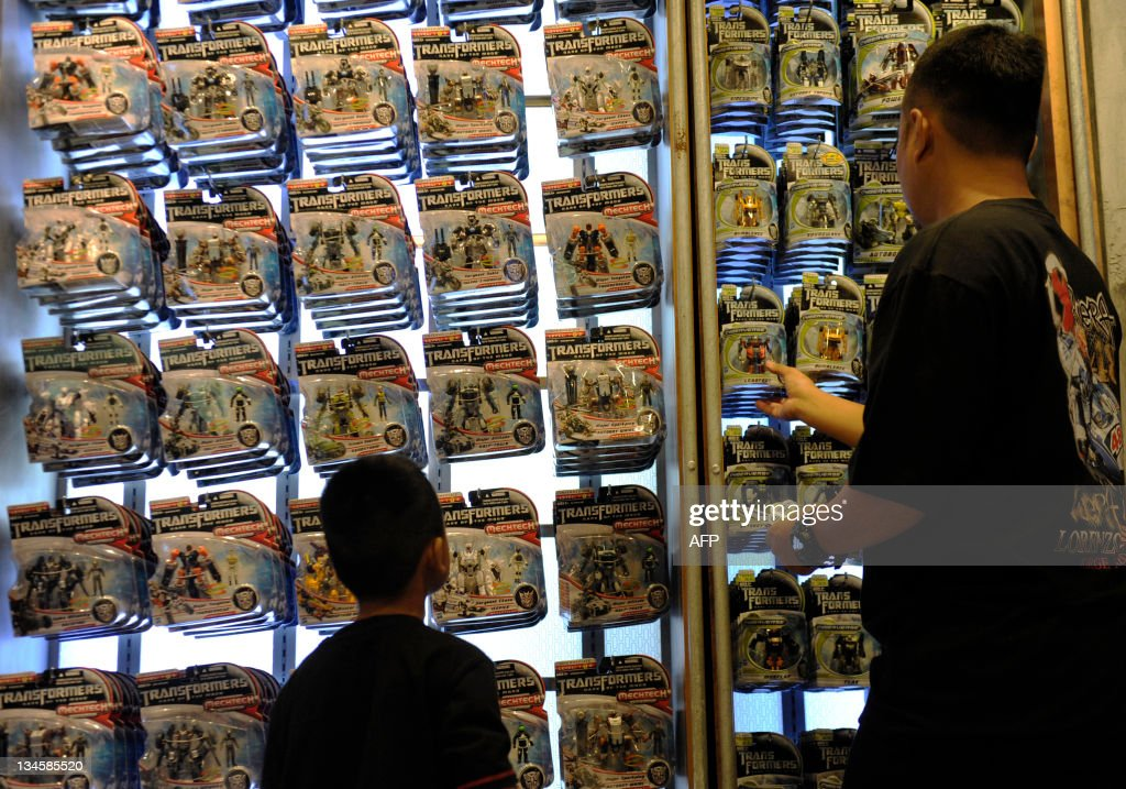 A father and son browse Transformers merchandise at its themed amusement park ride at Universal Studios Singapore on December 3, 2011. 'Transformers: The Ride' is based on the Transformers movie franchise directed by Michael Bay.