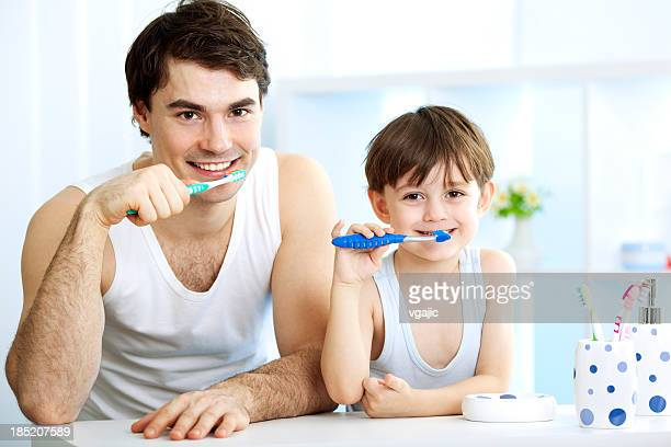 Father and son brushing teeth together.