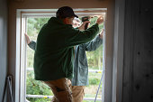 Father and son builders installing new window in house