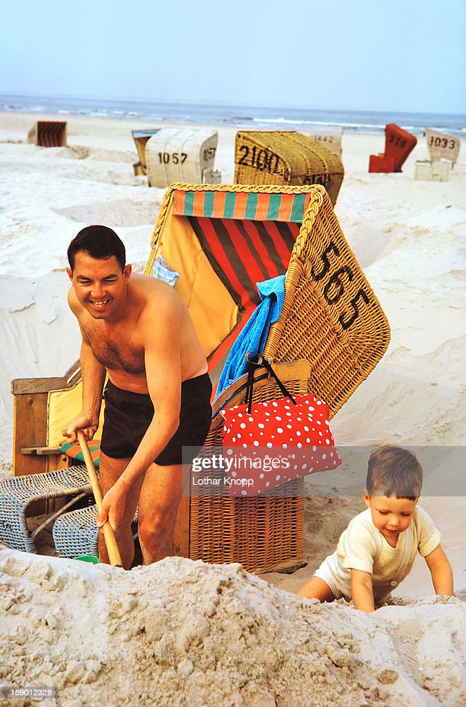 Father and son building a sandcastle : Stock Photo