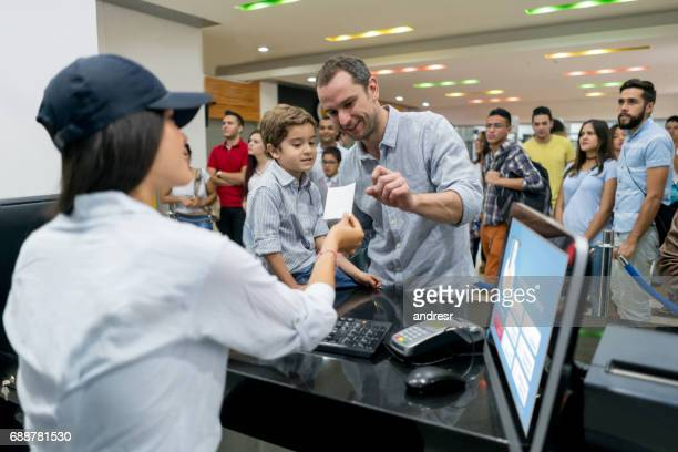 Father and son buying movie tickets at the cinema