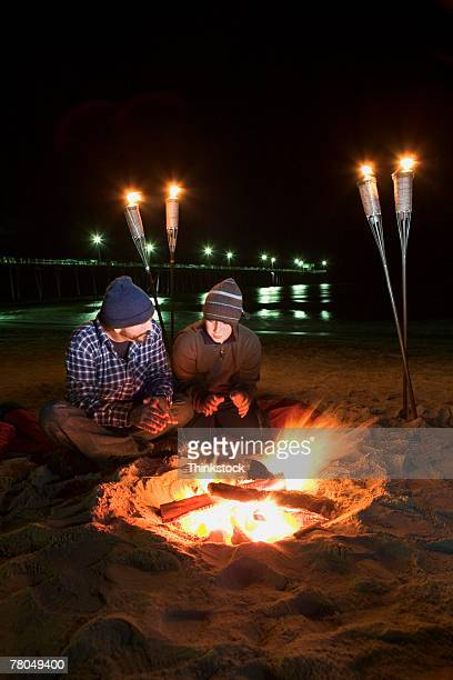 Father and son by campfire on beach