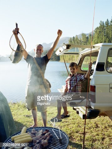 Father and son by lake with fishing tackle portrait stock for Wisconsin fishing license price