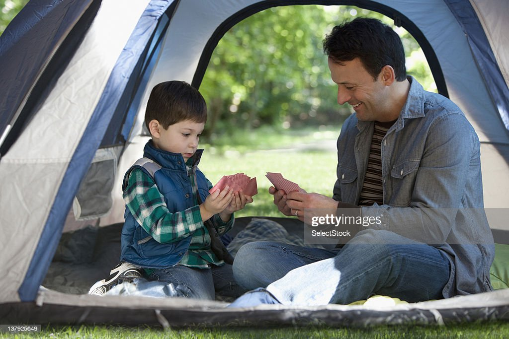 Father and son camping and playing cards : Stock Photo