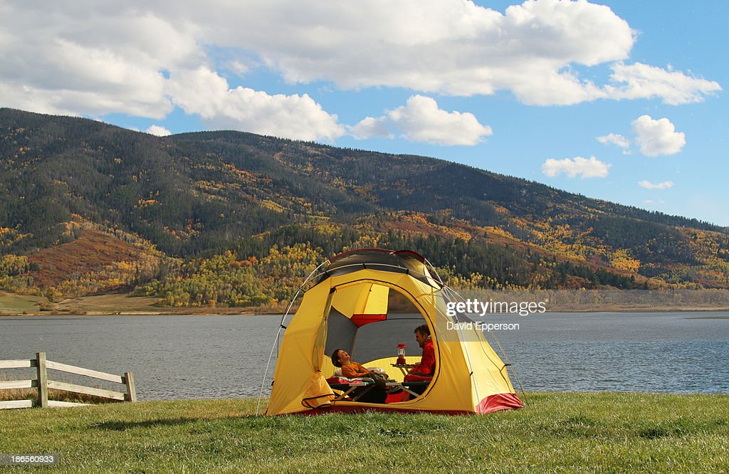Father and son camping by mountain lake : Stock Photo