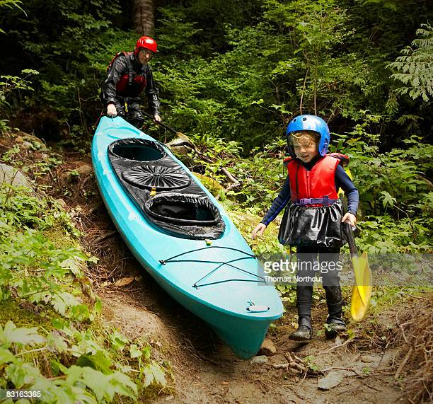 Father and son carrying kayak along forest trail