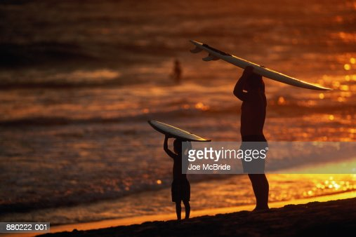 Father and son (3-5) carrying surfboards on heads at sunset : Stock Photo