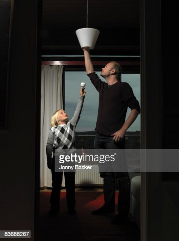 Father and son changing bulb : Stock Photo