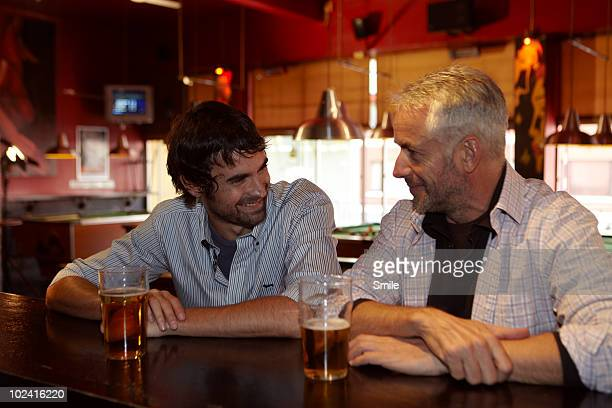 Father and son chatting in bar