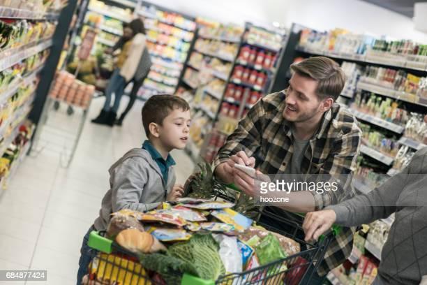 Vater und Sohn Überprüfung Einkaufsliste im Supermarkt