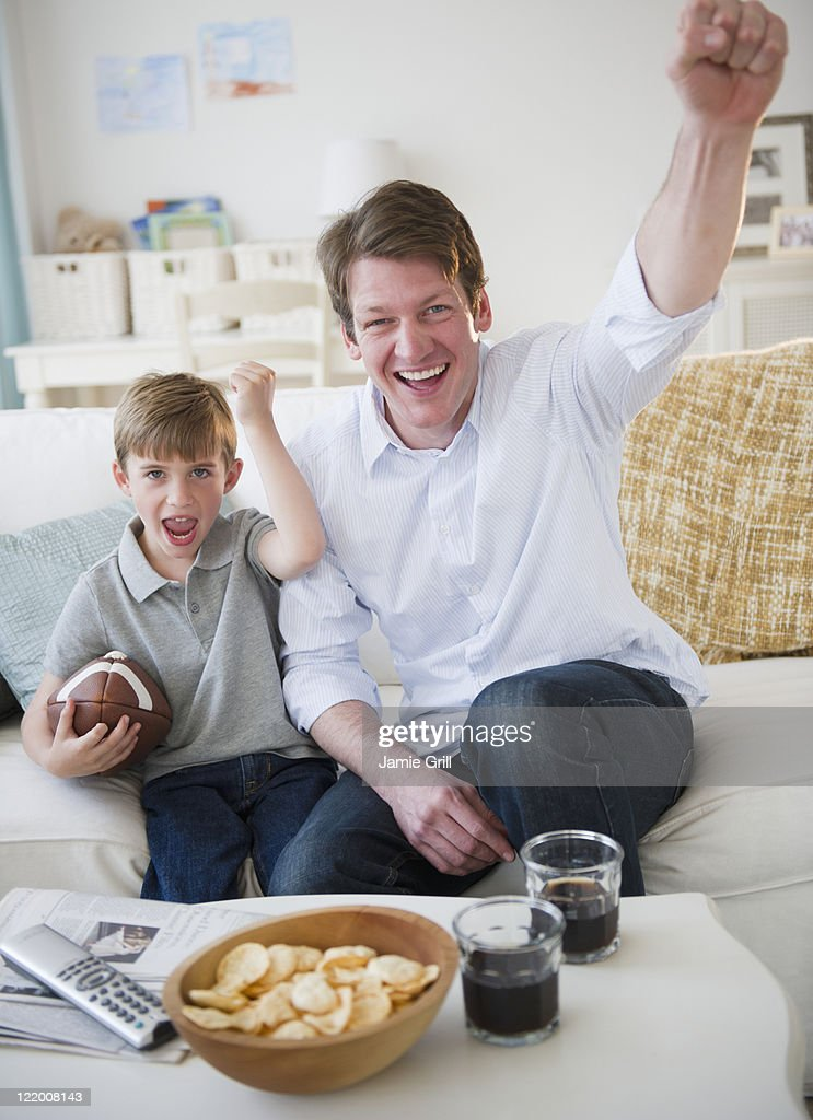Father and son cheering while watching TV : Stock Photo