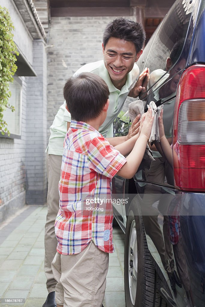Father and Son Clean their Minivan Together : Stock Photo
