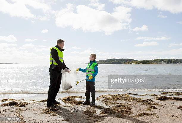 Father and son cleaning beach