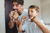 Little boy with his father in bathroom cleaning teeth with dental floss. Both looking in mirror and brushing teeth.