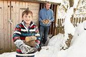Father And Son Collecting Logs From Wooden Store In Snow