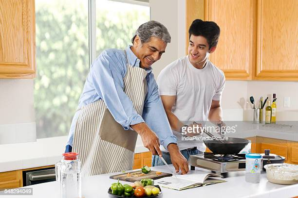 Father and son cooking food in the kitchen