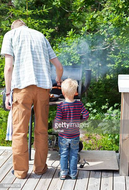 Father and son cooking sausage on an outdoor coal grill