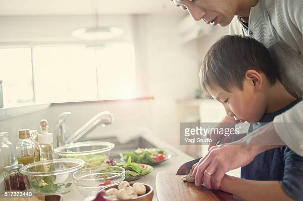 Father and son cooking together at home