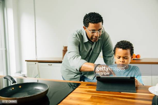 Father and son cooking with digital tablet in kitchen