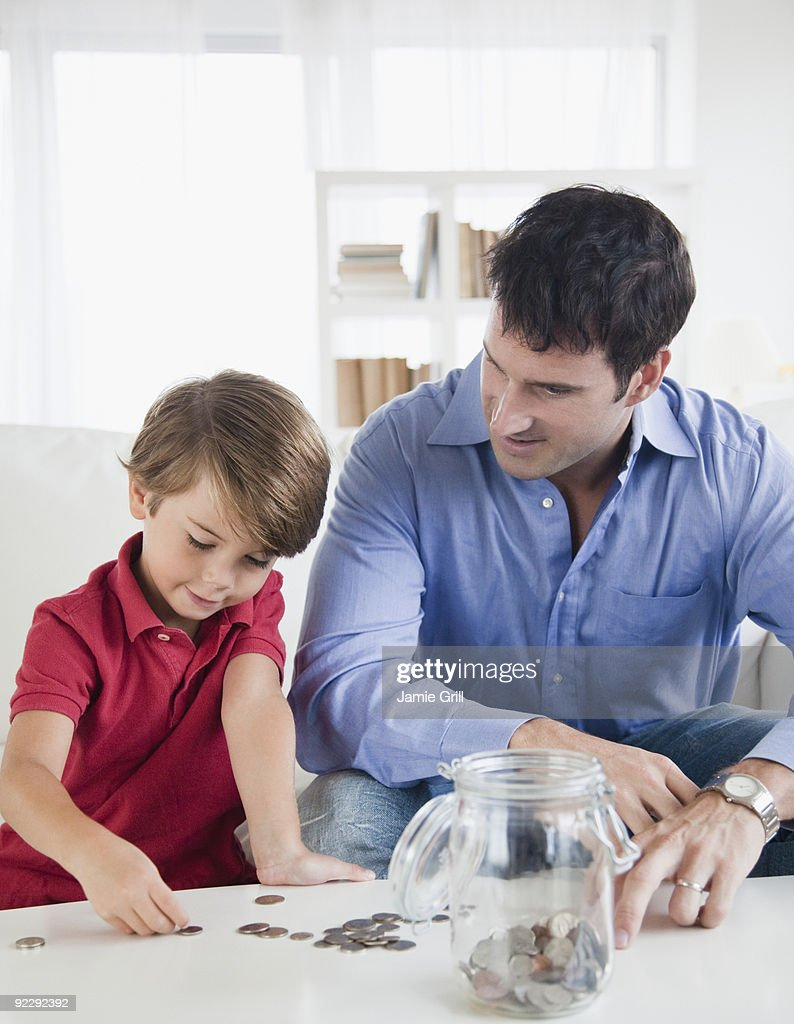 Father and Son counting coins together : Stock Photo