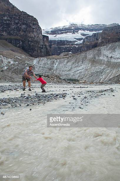 Father and son cross river below glaciated mountains