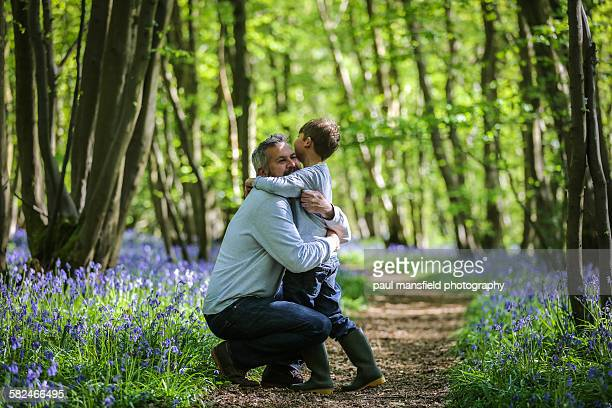 Father and son cuddle in bluebell wood