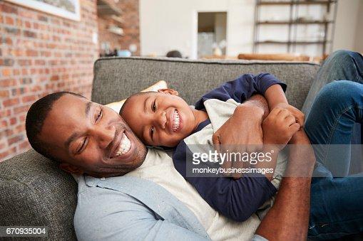 Père et fils câlins sur le canapé ensemble : Photo
