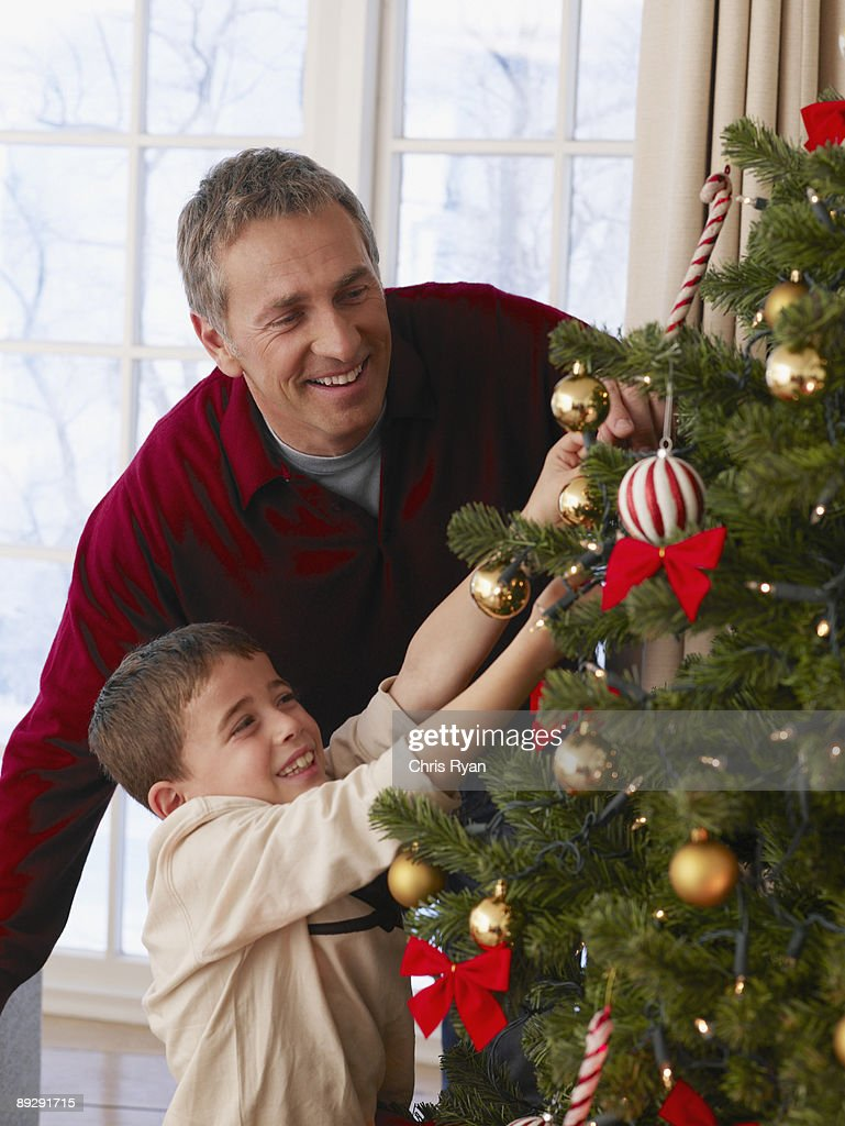 Father and son decorating Christmas tree : Stock Photo