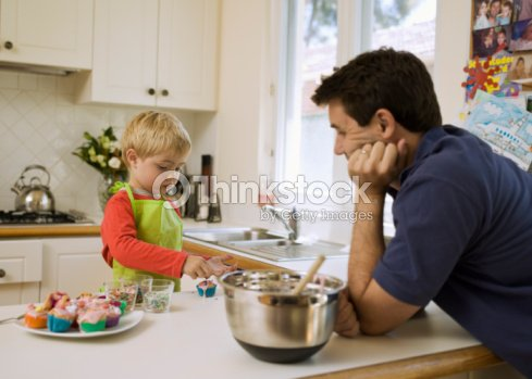 father and son decorating cupcakes stock photo