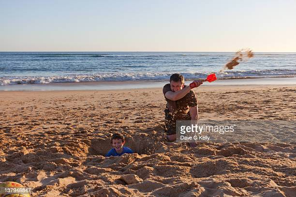 Father and son digging in beach