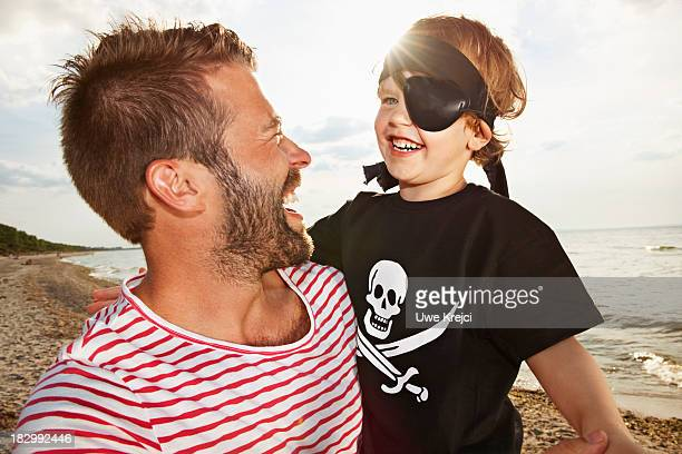 Father and son dressed as pirates on beach