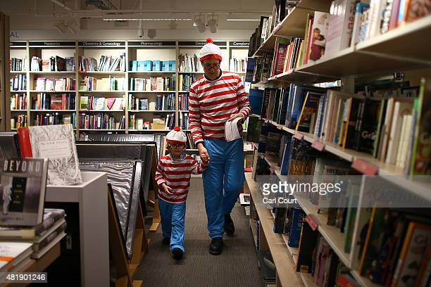 A father and son dressed as 'Where's Wally' characters also known as 'Where's Waldo' in North America take part in a competition to find Wally and...