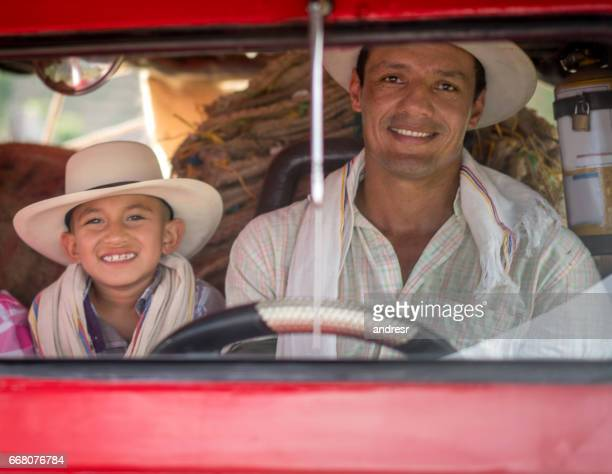 Father and son driving a car at the farm