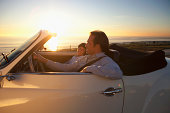 Father and son driving by ocean in convertible car