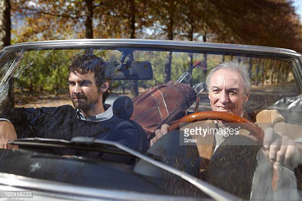 Father and son driving with golf clubs