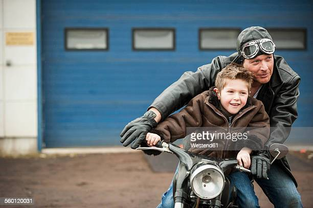 Father and son driving with vintage moped