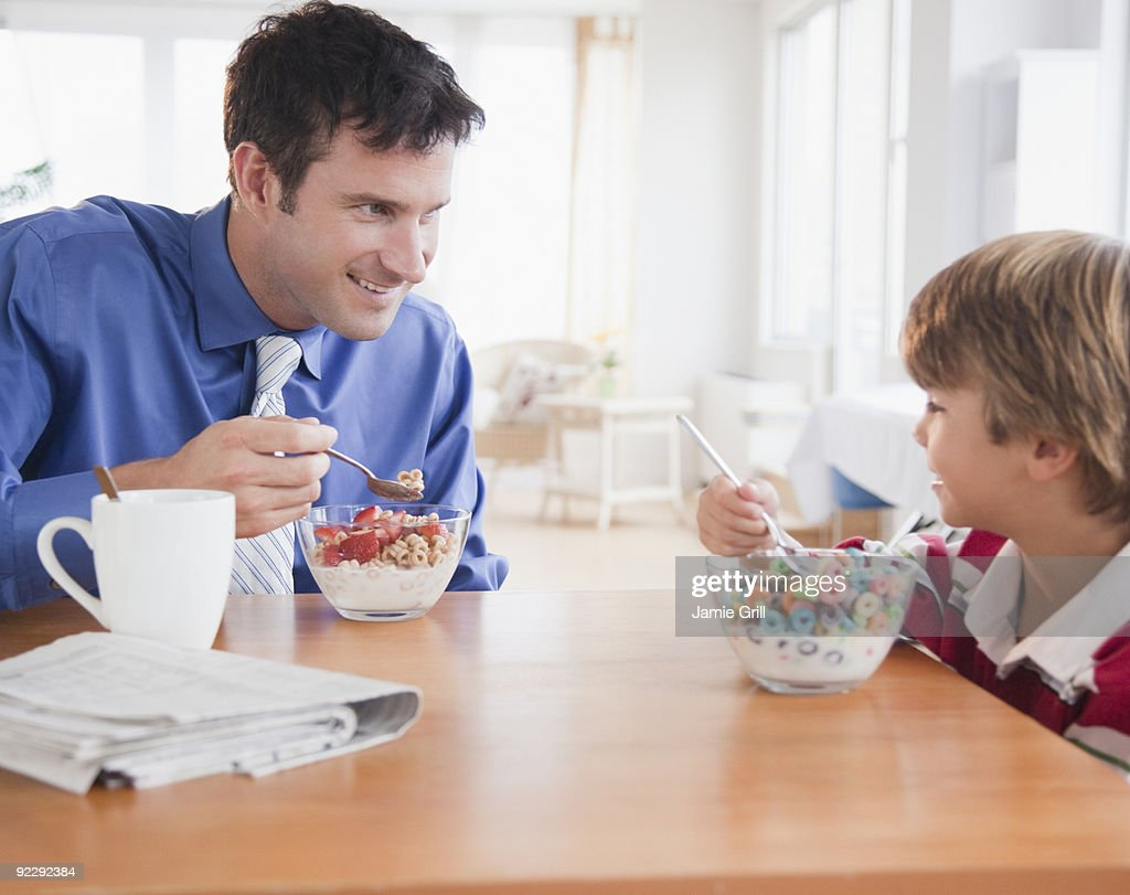 Father and son eating breakfast together : Stock Photo