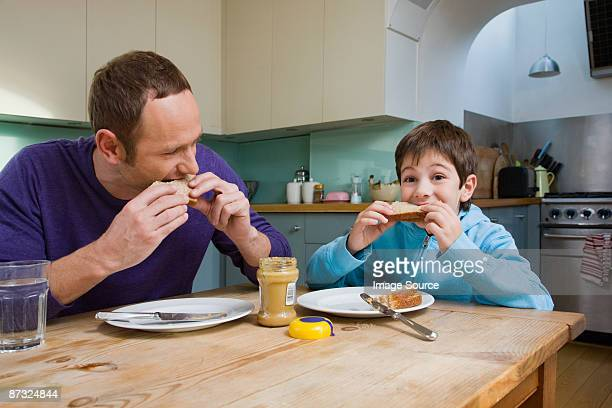 Father and son eating peanut butter sandwiches