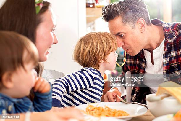 Father and son eating same peice of pasta