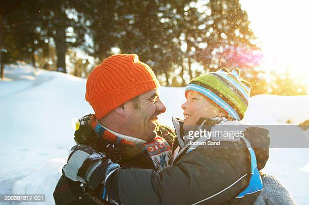 Father and son (8-10) embracing in snowy landscape, smiling, close-up