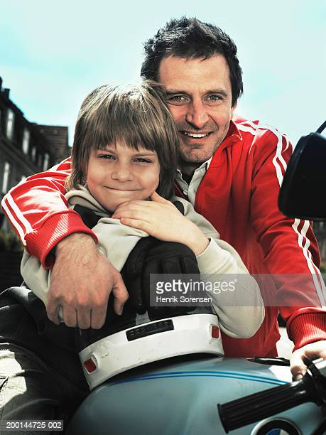 Father and son (9-11) embracing, leaning on motorcycle, portrait