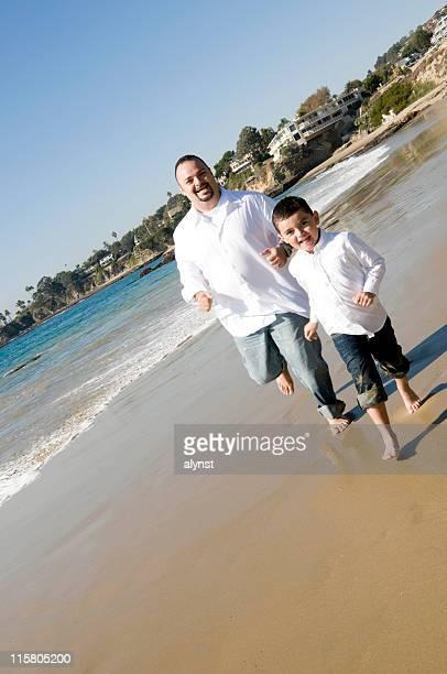 Father and Son Enjoy a Run Along the Beach