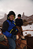 Father and son enjoy horse riding in winter in Utah