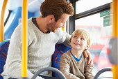 Happy Smiling Father And Son Enjoying Bus Journey Together
